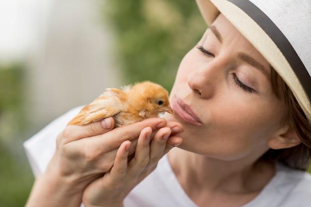 Woman holding a chick on a farm Free Photo