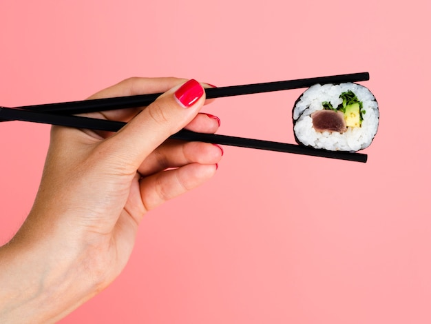 Woman holding in chopsticks a sushi roll on a rose background Free Photo
