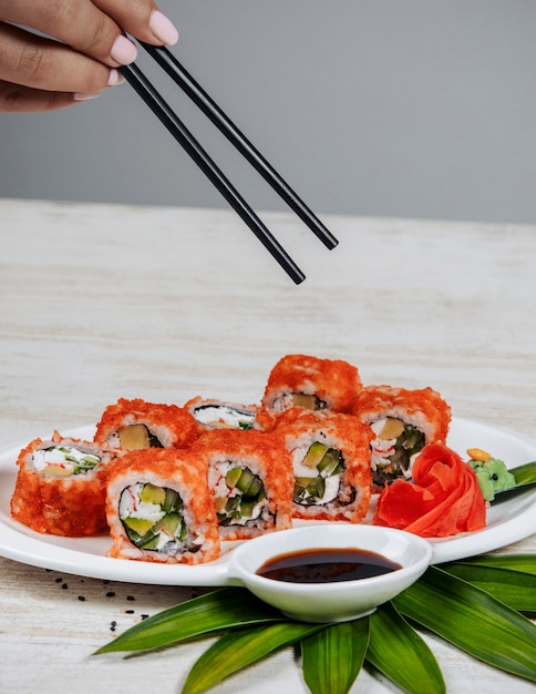 Woman holding chopsticks to take sushi rolls with red tobiko Free Photo
