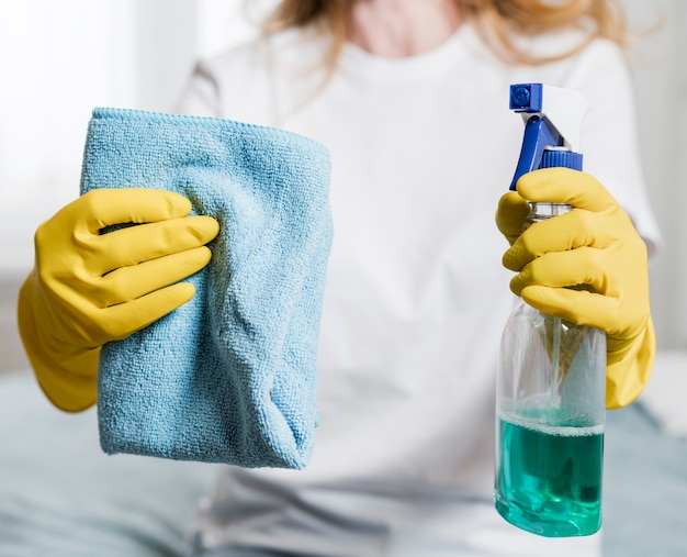 Free Photo | Woman holding cleaning product and rag