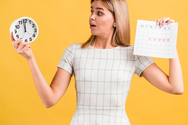 Woman holding a clock and her period calendar Free Photo