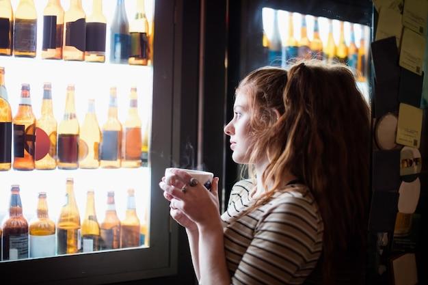コーヒーカップを保持しているとワインのディスプレイを見て女性 無料写真