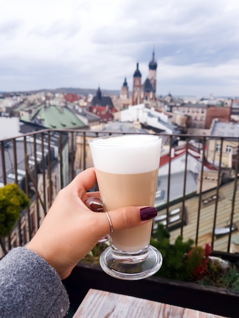 Woman holding coffee cup in cafe on a roof with view to st. mary's church krakow Premium Photo