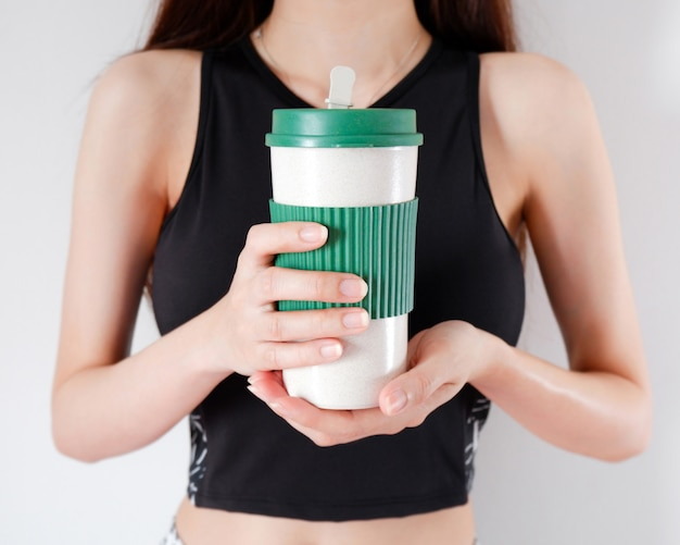 Woman holding a coffee cup in hands with exercises girls background. Premium Photo