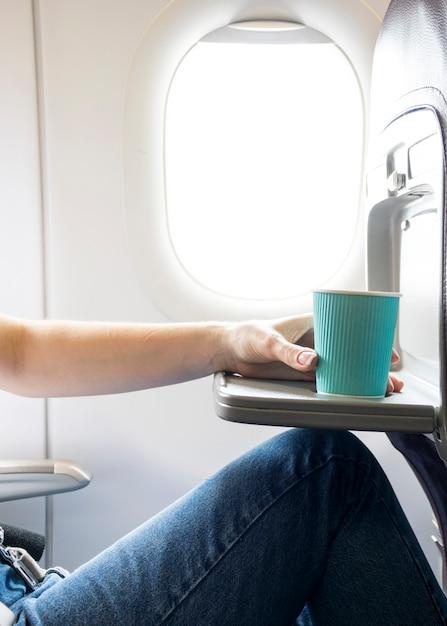 Женщина держит чашку кофе в самолете Premium Фотографии
