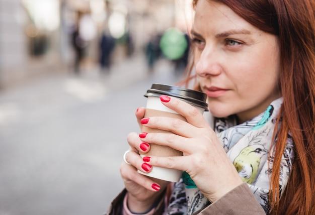 ぼやけた通りにコーヒーカップを保持している女性。晴れた春の午後。赤いマニキュア。コーヒーの紙コップを持つ女性の手は奪います。 Premium写真