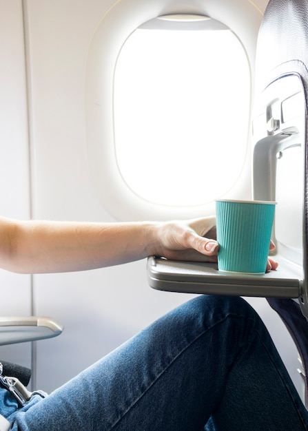 Woman holding coffee cup in plane Free Photo
