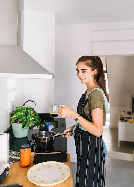 Woman holding coffee mug in hand preparing food in the kitchen Free Photo