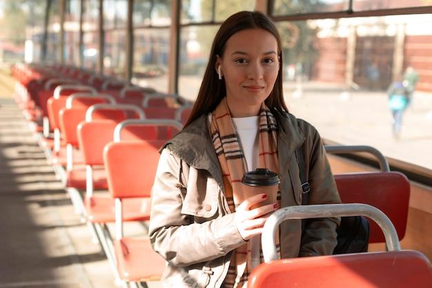 Donna che tiene un caffè nel trasporto pubblico del tram Foto Gratuite