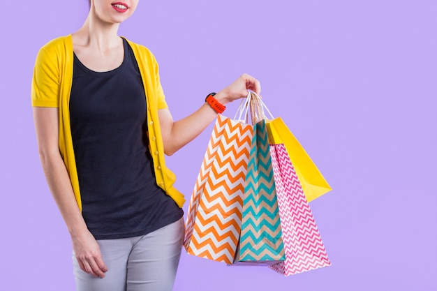 Woman holding colorful paper shopping bag against purple wallpaper Free Photo