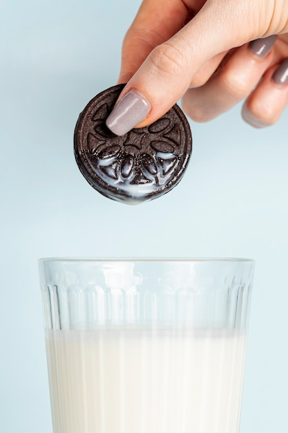 Woman holding a cookie above glass of fresh milk Free Photo