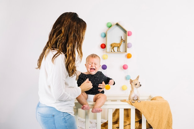 Woman holding crying baby near dog Free Photo
