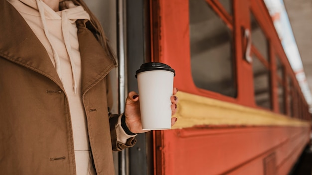 Woman holding a cup of coffee next to train Free Photo