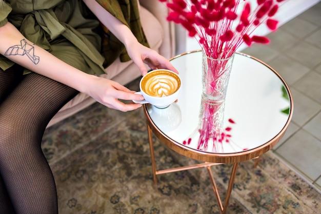 おいしいカプチーノのカップを保持している女性とレストラン、派手な雰囲気、コーヒー愛好家での時間をお楽しみください。 無料写真