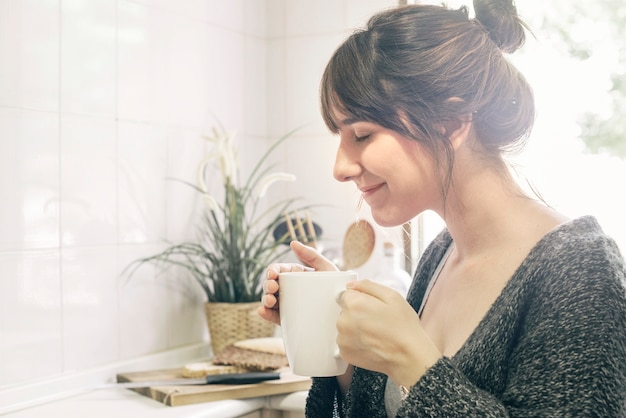 Woman holding cup smelling coffee Free Photo
