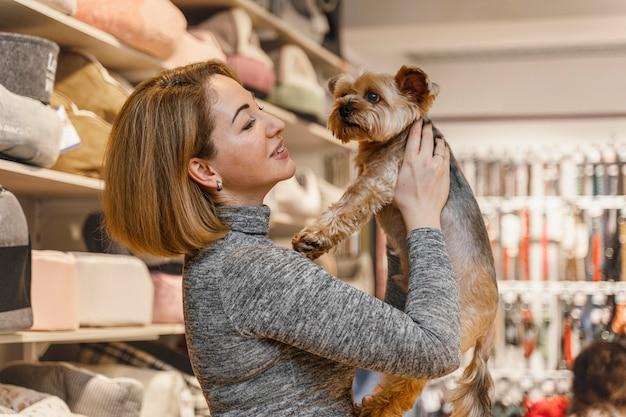 Donna che tiene un simpatico cagnolino presso il negozio di animali Foto Gratuite