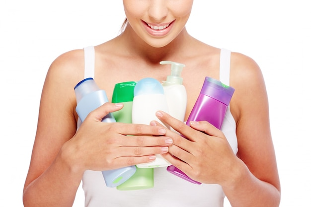Woman holding different lotions Free Photo