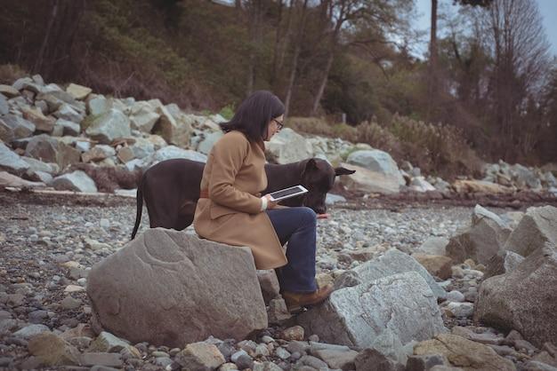 ビーチで犬のデジタルタブレットを保持している女性 無料写真