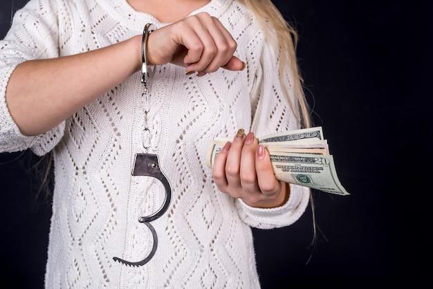 Woman holding dollar bills in handcuffs Premium Photo