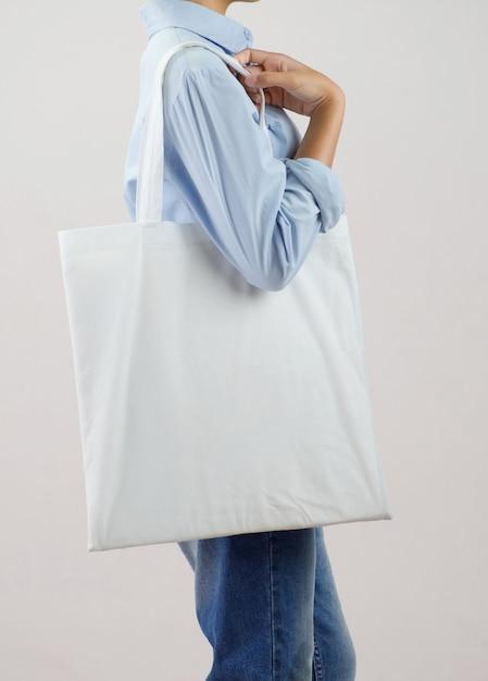 Woman holding eco fabric bag isolate on gray background Premium Photo