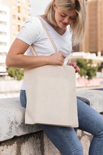 Donna che mantiene una borsa in tessuto guardando verso il basso Foto Gratuite