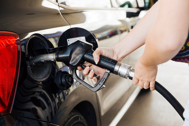 Woman holding filling gun in hands and fueling car Free Photo
