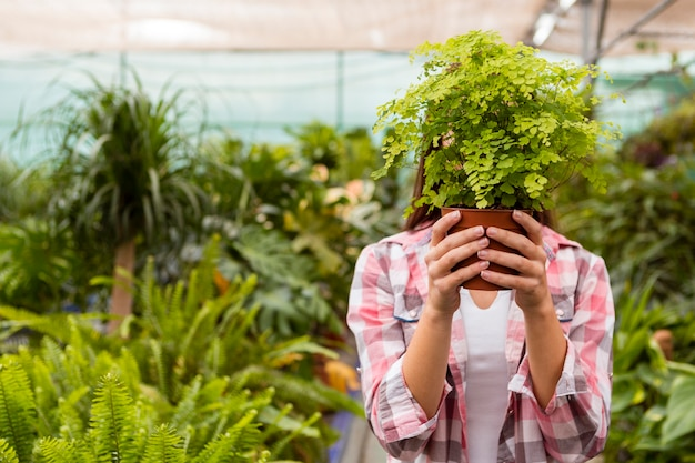 Woman holding flower pot covering head in garden Free Photo