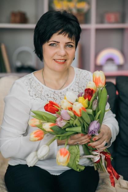 自宅で手に花を持った女性 Premium写真