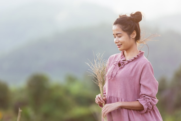 Woman holding flowers in the meadow. Free Photo