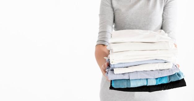 折り畳まれたランドリーコピースペースを保持している女性 Premium写真