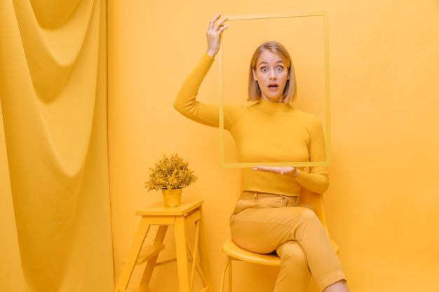 Woman holding frame around face in a yellow scene Free Photo