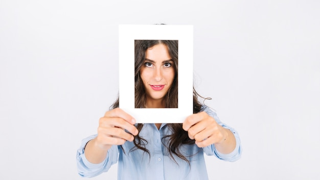 Woman holding frame in front of face Photo | Free Download