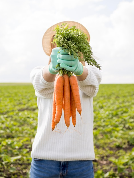 Woman holding in front of her carrots Premium Photo