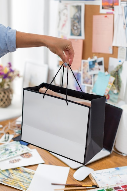 Woman holding gift bag over desk Free Photo
