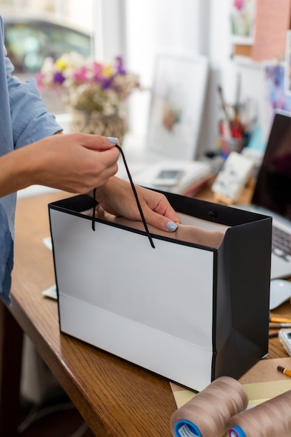 Woman holding gift bag on desk Free Photo