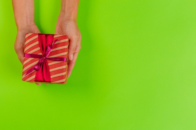 Woman holding gift box on color Premium Photo