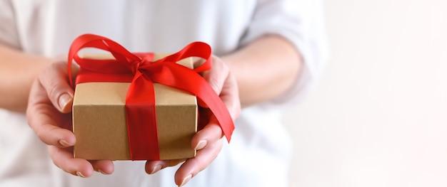 Женщина держит подарочную коробку с красным бантом Premium Фотографии