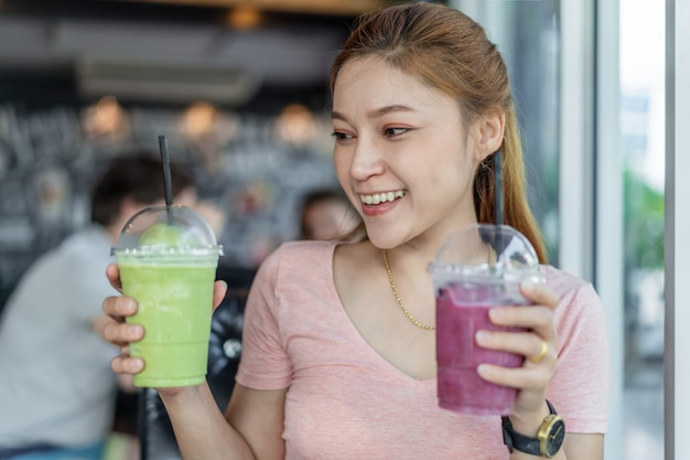 Woman holding glass of green tea frappe and blueberry smoothies Premium Photo
