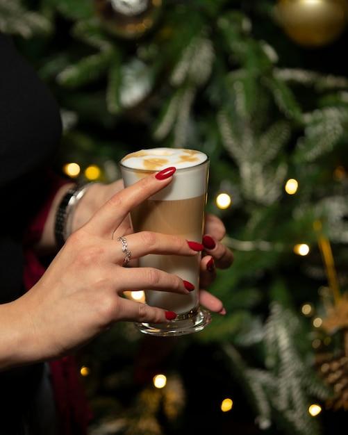 Woman holding glass of latte macchiato with foam Free Photo