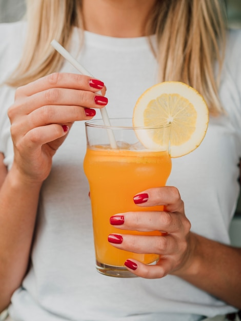 Woman holding a glass of orange juice and straw Free Photo