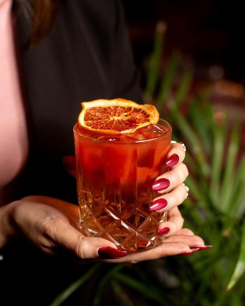 Donna che tiene un bicchiere di cocktail rosso guarnito con una fetta d'arancia essiccata Foto Gratuite