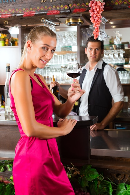 Woman holding a glass of wine in hand at the bar Premium Photo