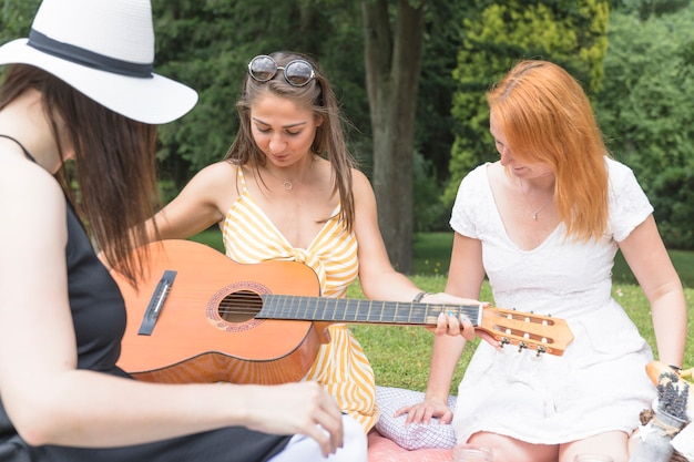 Woman holding guitar sitting with her friends in the park Free Photo
