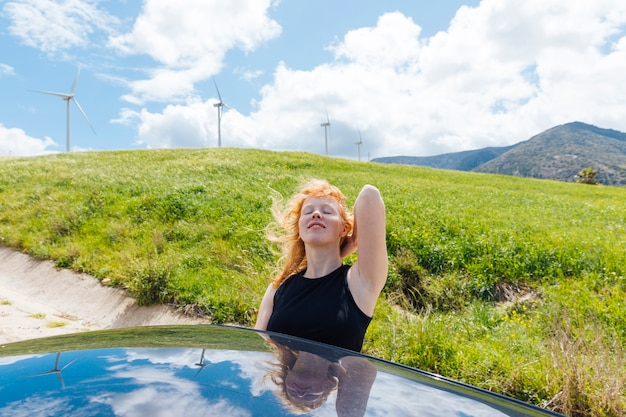 Woman holding hair and enjoying sun out of car window Free Photo