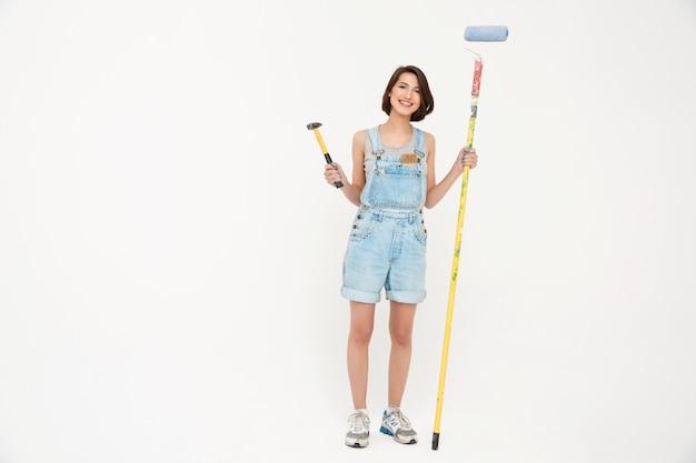家を改装するハンマーとペイントブラシを保持している女性 無料写真