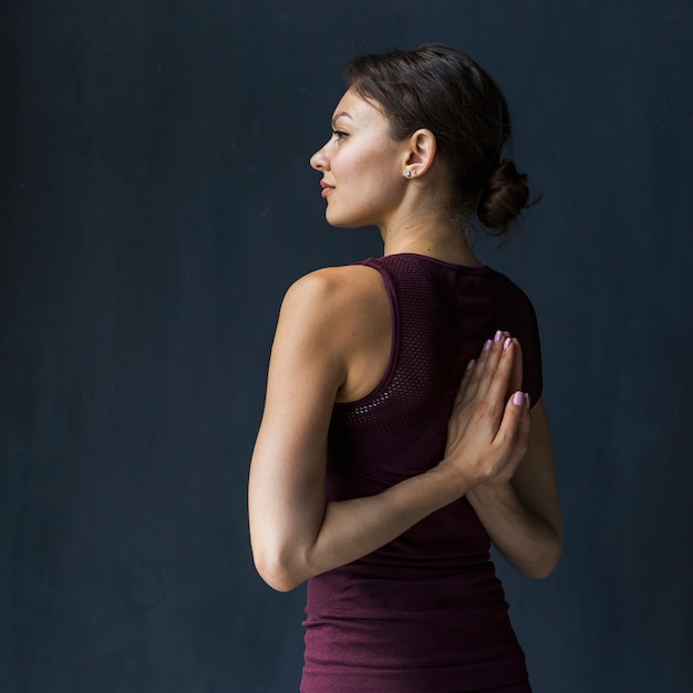 Woman holding hand in a praying pose behind her back Free Photo