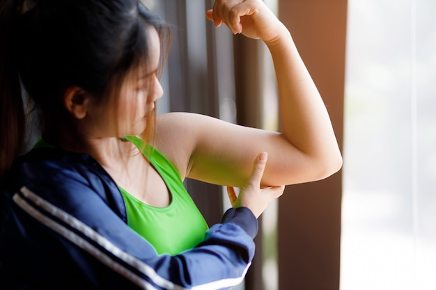Woman holding a hand with excess fat. concept of unhealthy lifestyle. Premium Photo