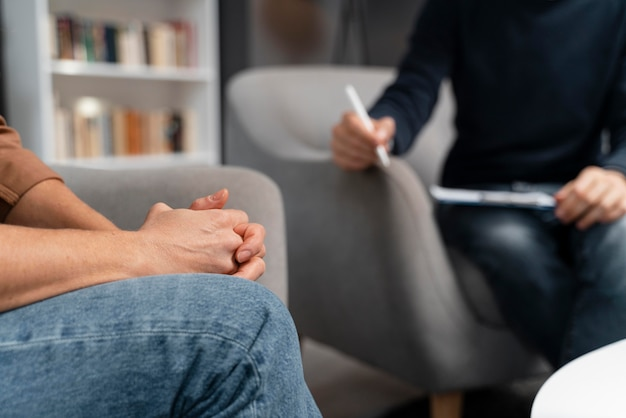Woman holding hands together talking with counselor Free Photo