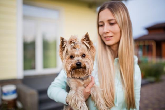 Woman holding hands yorkshire terrier dog outdoor Premium Photo