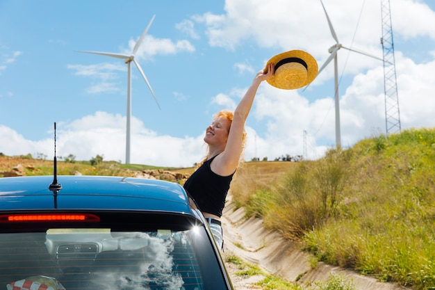 Woman holding hat in arm outstretched out of car window Free Photo